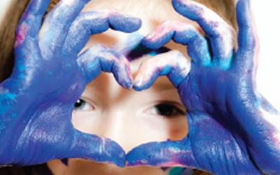 Girl with painted blue hands looking through her fingers making a love heart shape