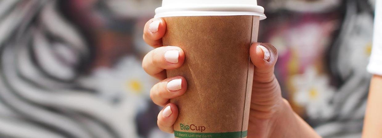 hand holding a kraft coffee cup