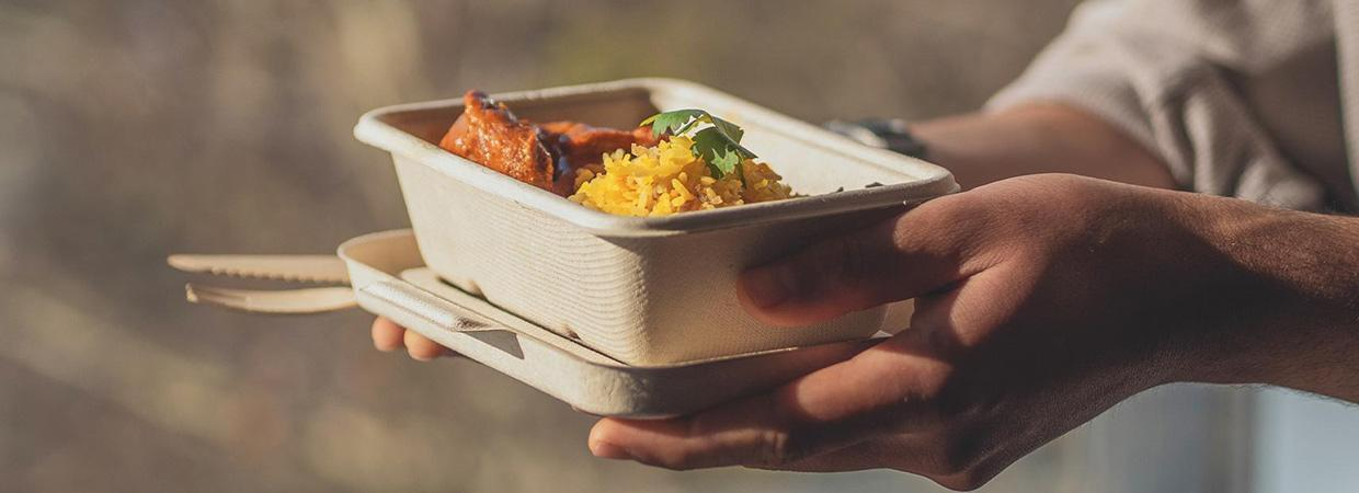 Man holds a 600ml brown sugarcane takeaway food container and lid with curry and rice inside.
