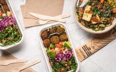 BioPak sugarcane pulp containers with PLA lids with falafels and salad, alongside wooden knives and forks