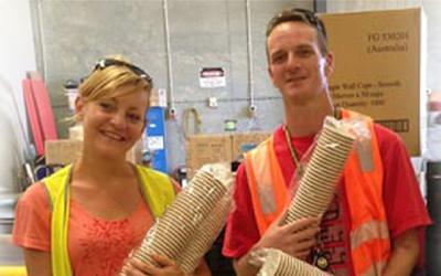 Two people holding tower of paper cups