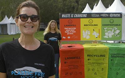 lady happily showing the compost bins at an event