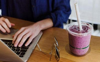 Woman on a laptop with a fresh shake in a cold cup on her side