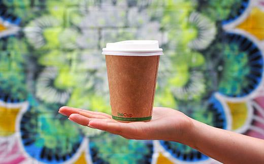 person-holding-coffee-up-against-colourful-backdrop-post
