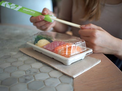 girl holding chopsticks with sushi in sugarcane sushi tray on table