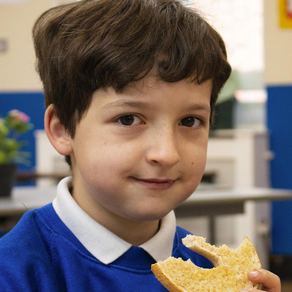 child holding a load bread