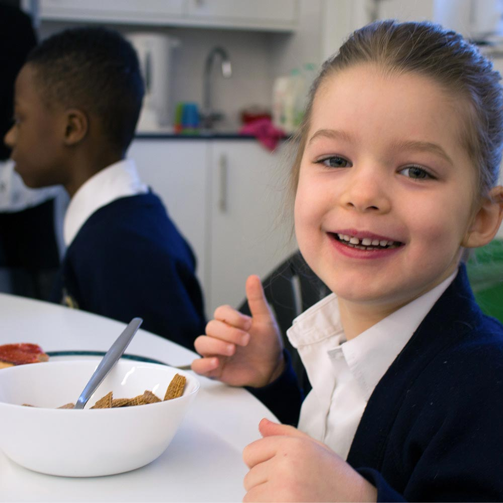 child looking very happy with the food she ate
