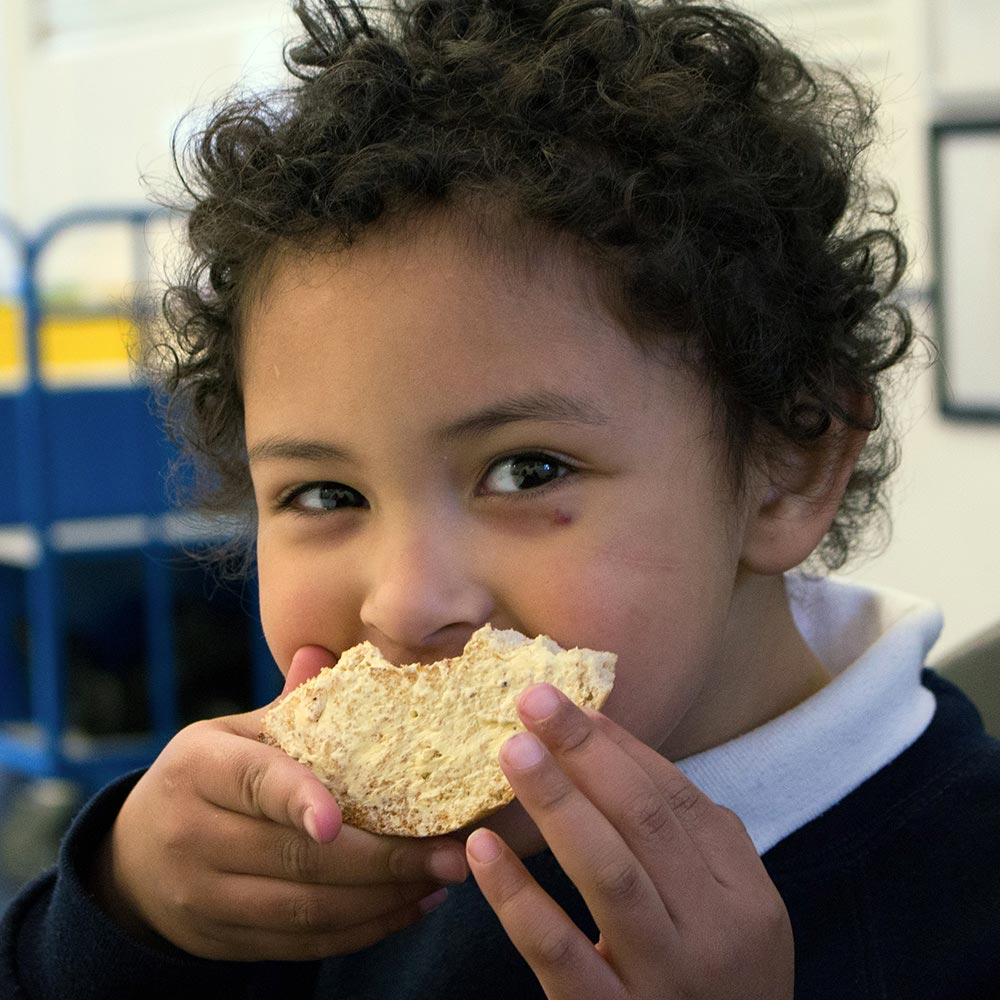 a child looking very happy eating his bread